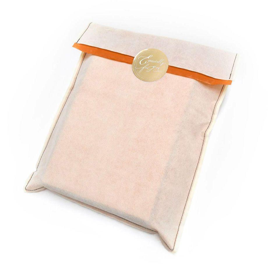 オレンジがアクセントになったアイボリーの不織布にゴールドのシールでとめるラッピング