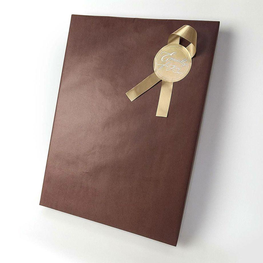 シックなブラウンの包装紙にゴールドのリボンシールをつけたラッピング