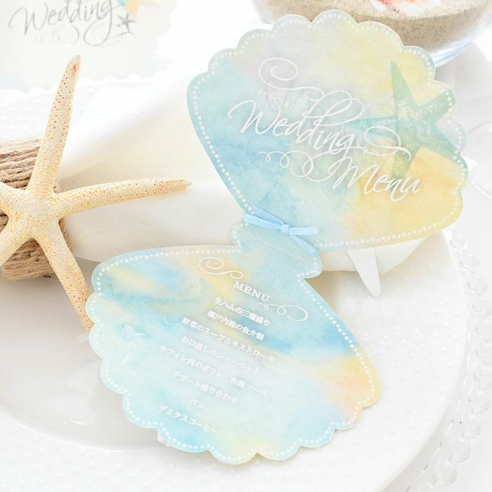 貝をかたどったロマンチックなデザインにスターフィッシュ型のお名前タグをつけた席札メニュー表