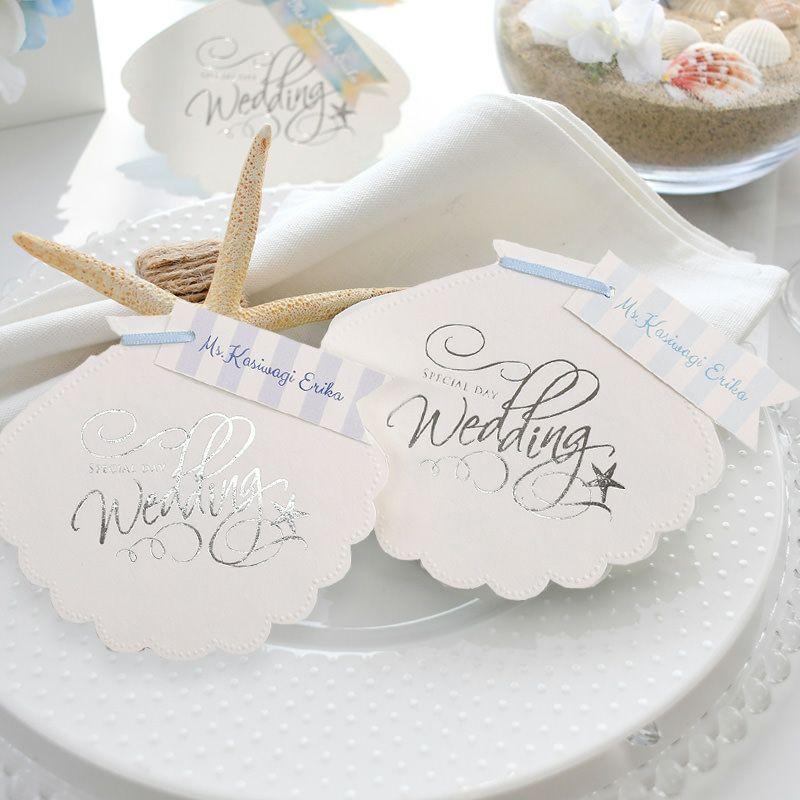 貝をかたどったロマンチックなデザインに爽やかストライプのお名前タグを付けた席札メニュー表