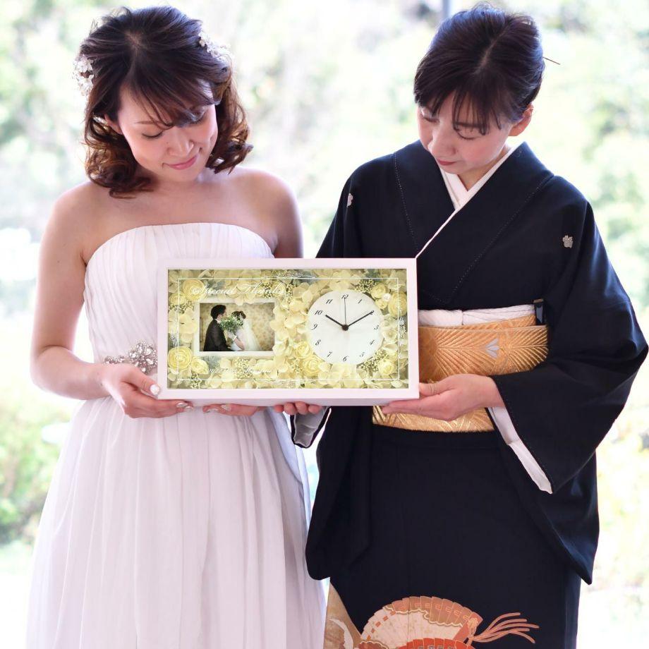 結婚式の両親贈呈品にフォトフレーム付きの花時計を贈る花嫁