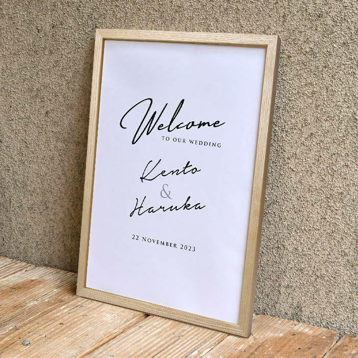フォントのみで構成されたミニマルデザインとナチュラルな木製フレームのウェルカムボード