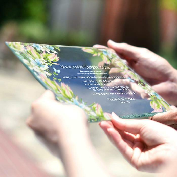 ブルースターのデザインをUV印刷したガラスの結婚証明書を手に持つ新郎新婦
