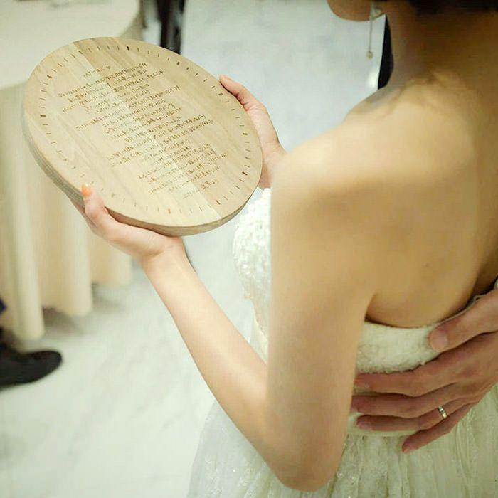 木製の花嫁の手紙に刻印された直筆のメッセージを読む花嫁
