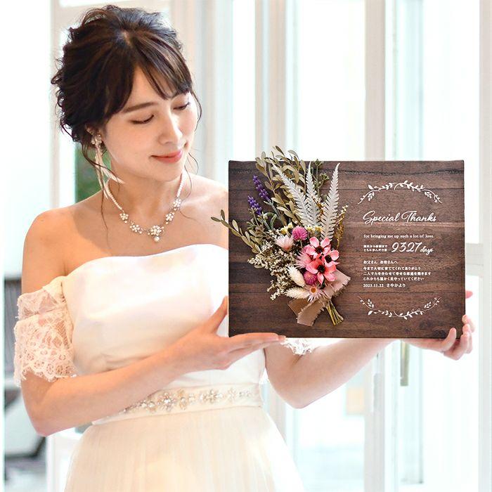 キャンバス地にブーケをアレンジした子育て感謝状を手にする花嫁