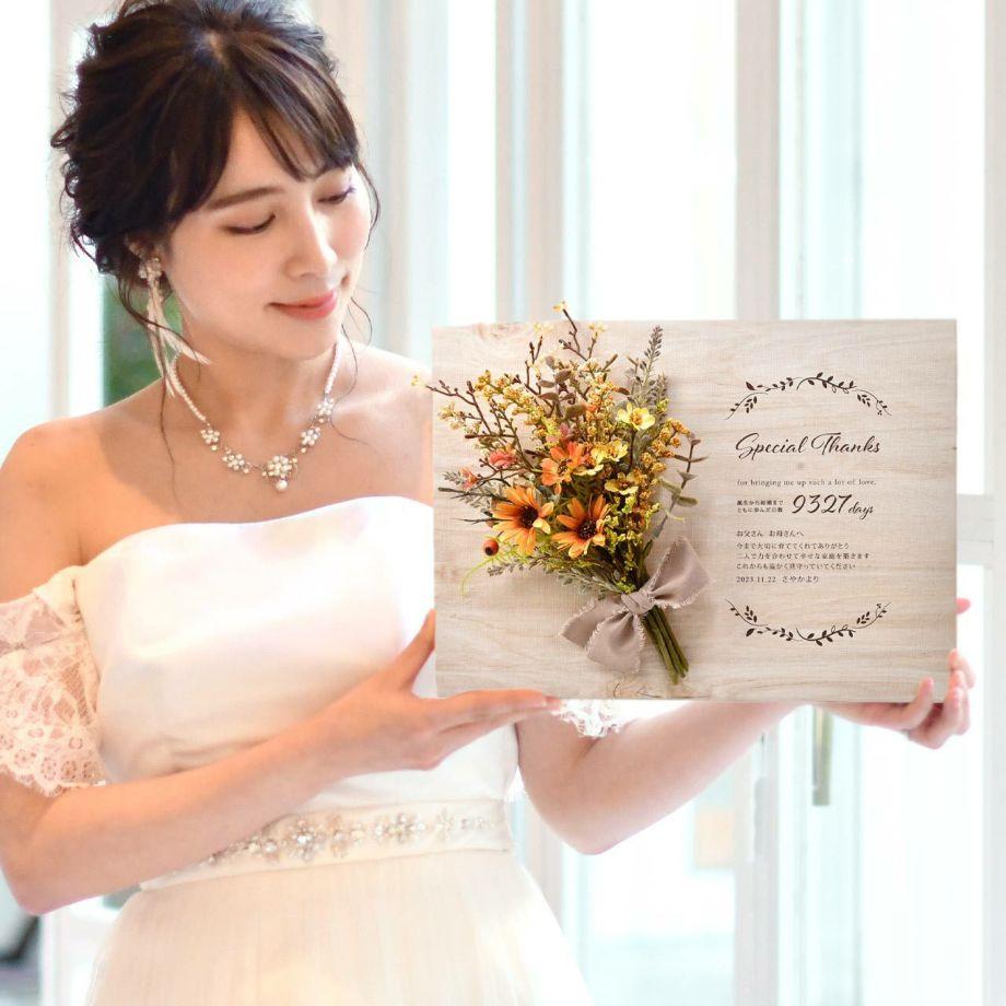 キャンバス地にオレンジ色のブーケをアレンジした子育て感謝状を手にする花嫁