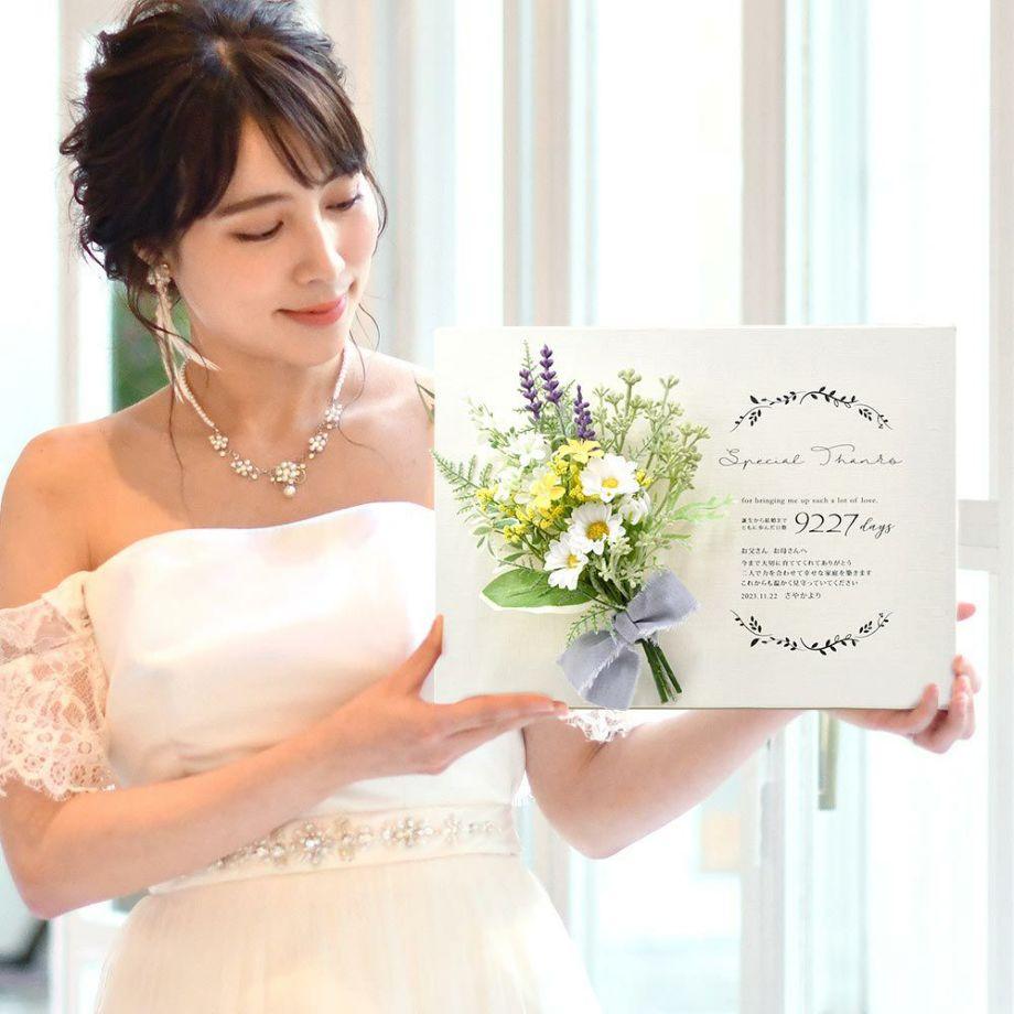 キャンバス地にスワッグ風ブーケをアレンジした子育て感謝状を手にする花嫁