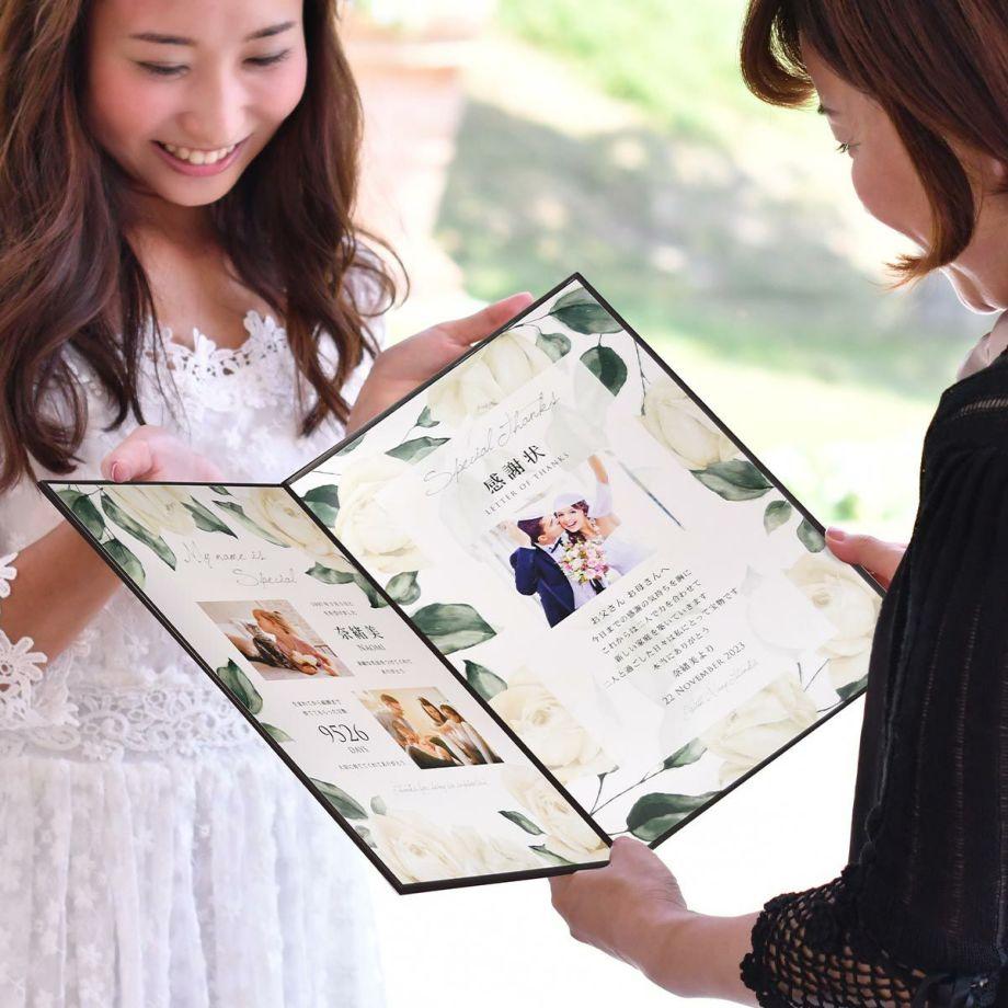 結婚式披露宴の両親贈呈シーンで子育て感謝状を渡す花嫁